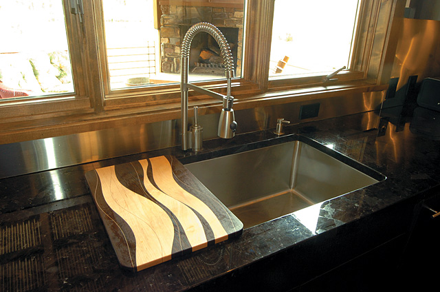 """When Mitzi Franklin set out to choose materials for her home in Steamboat, she selected the exotic black coffee color of Wenge wood from West Africa for the kitchen cabinets. She knew she wanted granite rather than marble countertops for the durability of the stone and found what she wanted in a color called """"maroon Bahia."""""""