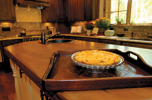 Phyl trusted her instincts and, despite the urging of her kitchen designer, chose a large distressed wooden  countertop for the jumbo cooking island. Every new scratch and ding merely adds character.