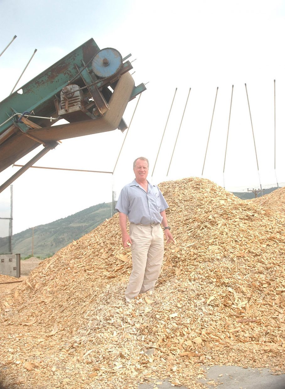 Phelps Lane, with Kremmling-based wood pellet mill Confluence Energy, stands in a pile of wood chips that will be turned into pellets.