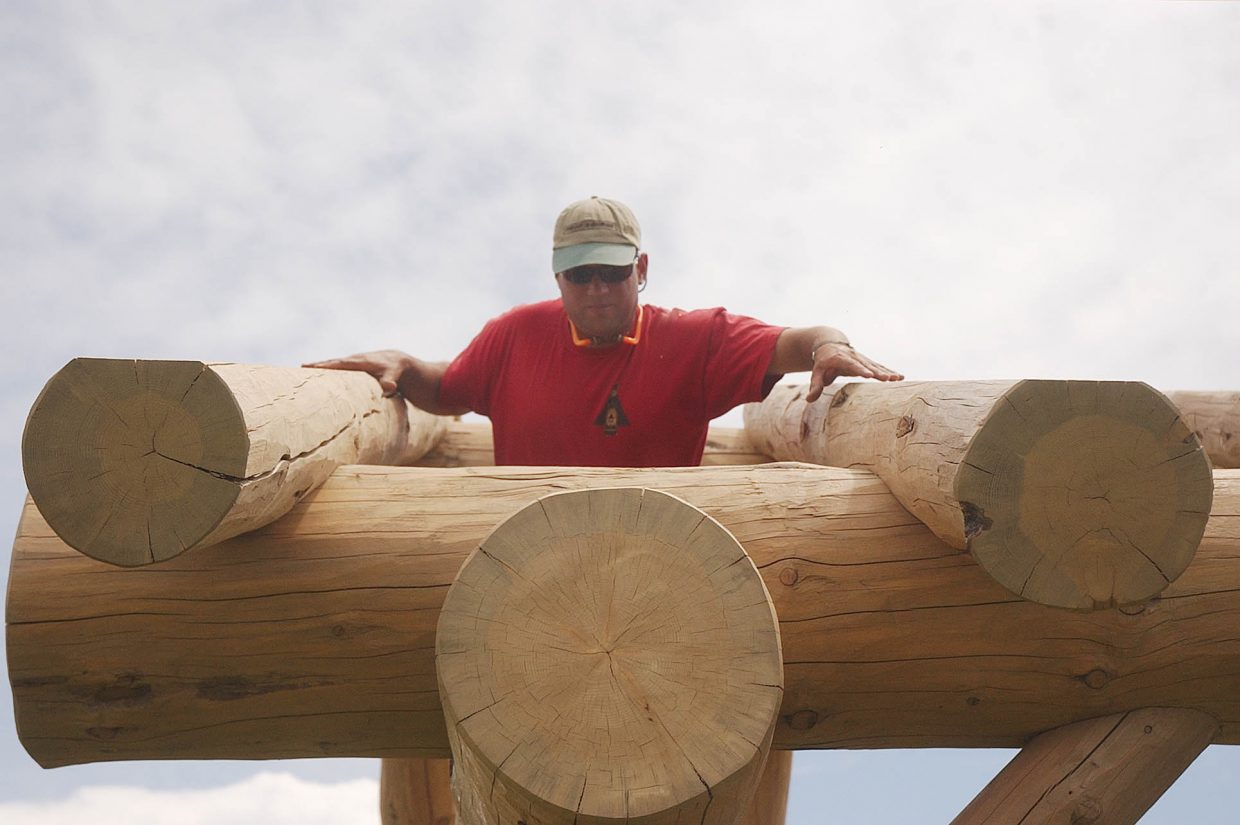 Steve Yanoski, with Scribeline Timberworks Inc. in Steamboat Springs, constructs a structure made out of lodgepole pine at a picnic area in West End Village subdivision.