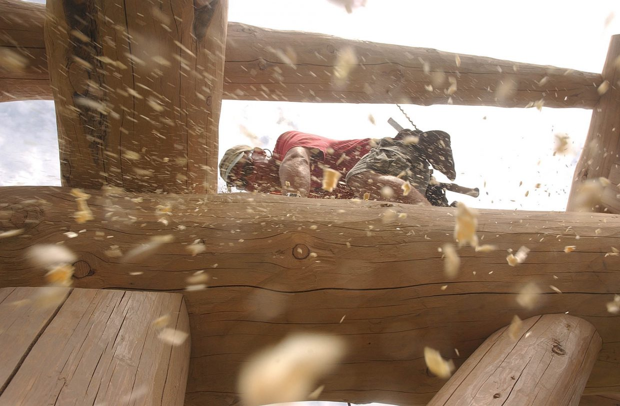 Steve Yanoski, with Scribeline Timberworks Inc. in Steamboat Springs, brushes wood shavings from a structure built in West End Village subdivision.
