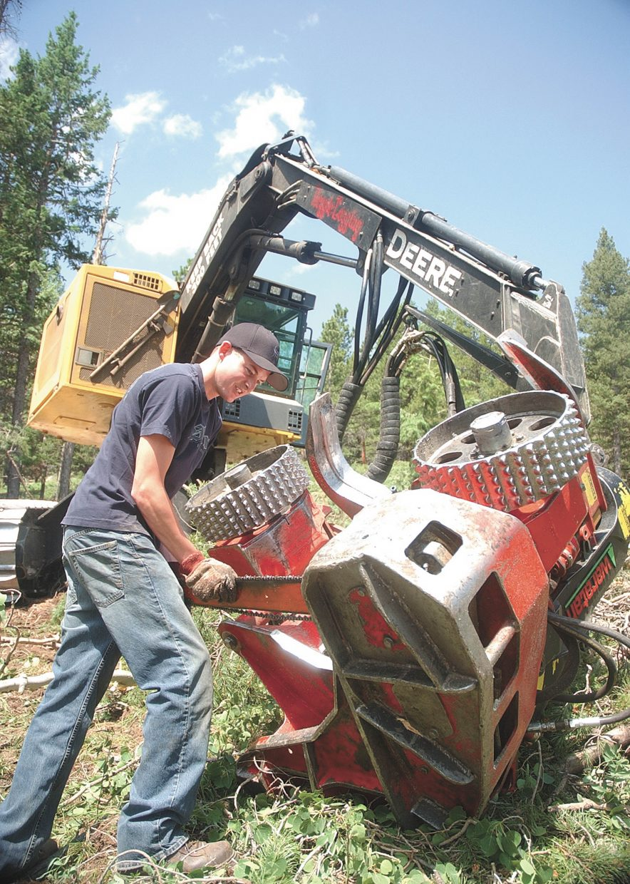 Beau Heggie, with Heggie Logging, replaces a chain on the harvester at a Roosevelt National Forest logging site.