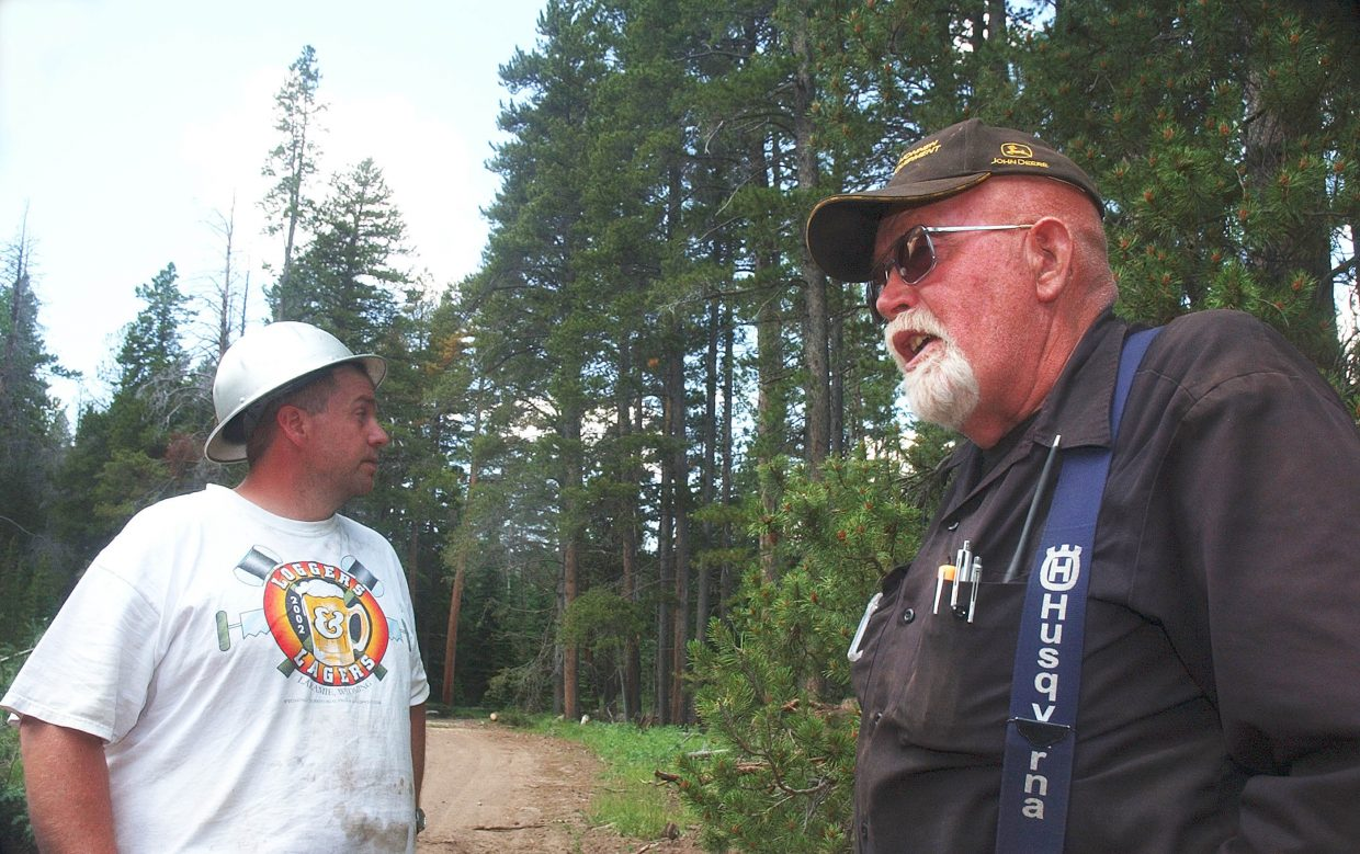 """Jerry Heggie, left, and Frank """"Red"""" Peters, with Wyo.-based Heggie Logging, talk about the logging industry at a logging site in the Roosevelt National Forest."""