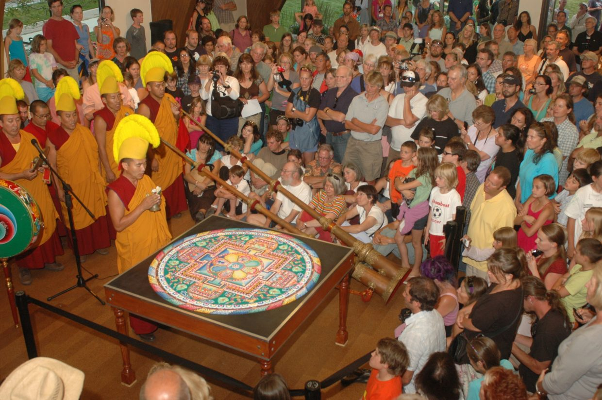A member of the Drepung Loseling monks with the compassion Buddha mandala before more than 300 intensely curious onlookers in Library Hall at Bud Werner Memorial Library on Wednesday night. The program continued with a short parade on 13th Street and a riverside ceremony at the Steamboat Spring.