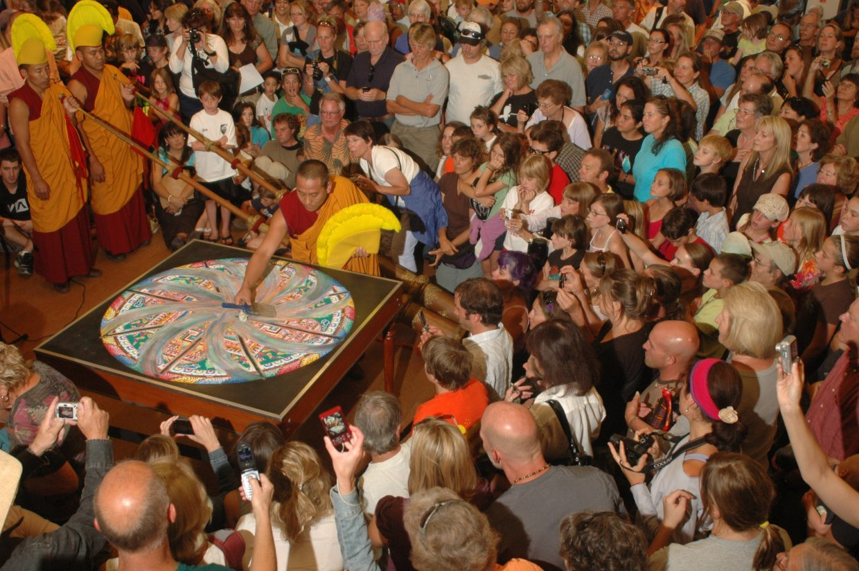 A member of the Drepung Loseling monks begins the transformation of the compassion Buddha mandala before more than 300 intensely curious onlookers in Library Hall at Bud Werner Memorial Library on Wednesday night. The program continued with a short parade on 13th Street and a riverside ceremony at the Steamboat Spring.