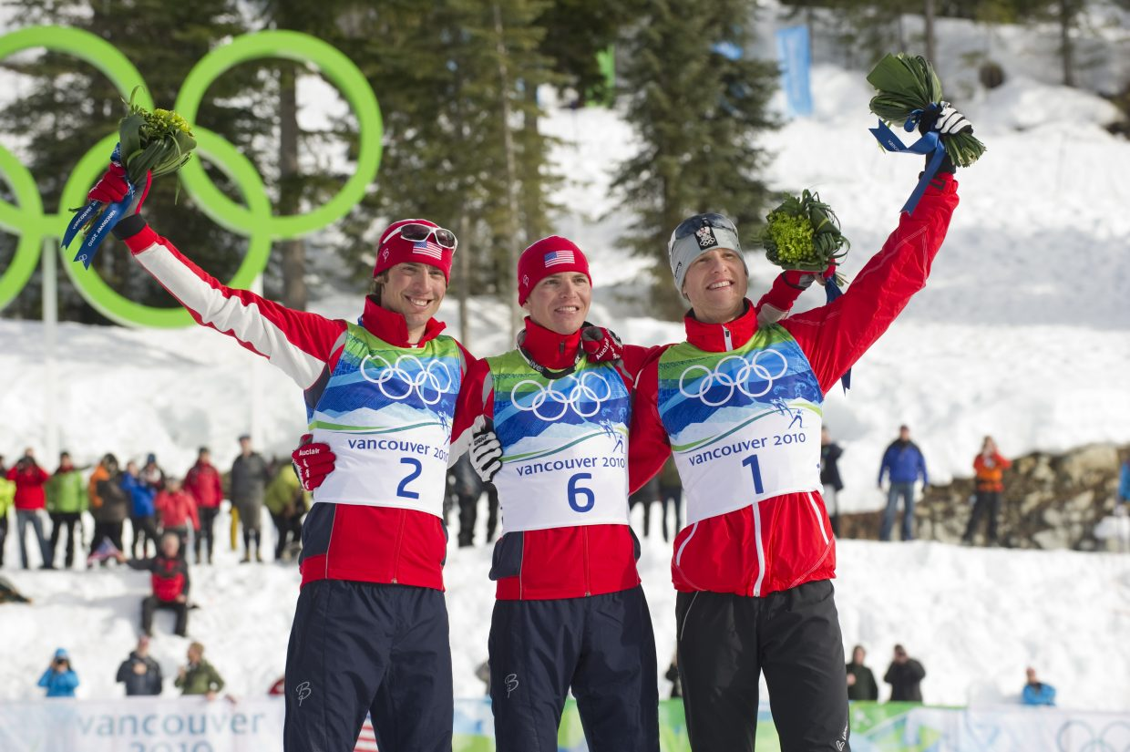 U.S. Nordic Combined Ski Team member and gold medalist Billy Demong, middle, stands on the flower ceremony podium with his teammate Johnny Spillane, left, who won the silver, and Austrian skier Bernhard Gruber, who finished third in the race.