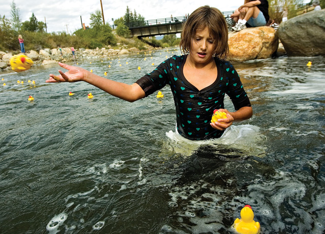 Eleven-year-old Savannah McKendrick helps toss a few floundering yellow rubber ducks back into the current after falling into the Yampa River on Saturday morning during the annual Rubber Ducky Race.