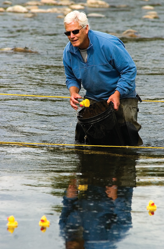 Tom Lake wades in the Yampa River as he collects some of the 2200 yellow rubber ducks floating downstream during the 20th annual Rubber Ducky Race in Steamboat Springs on Saturday morning.