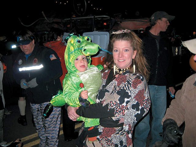 A child is cozy in a dragon costume during the downtown Halloween stroll on Lincoln Avenue in downtown Steamboat Springs.