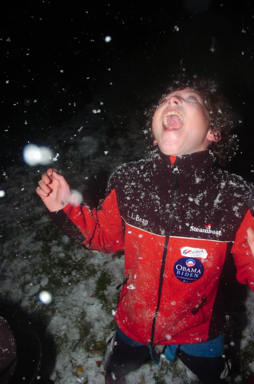 Nicholas Madden, 12, of Steamboat Springs, plays in the snow Tuesday night outside Big House Burgers, where Routt County Democrats were holding their election party.