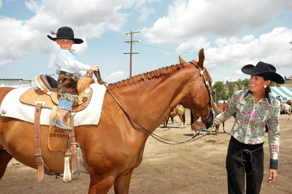 Julie Wernsman, of Craig, leads her son, Kacey Wernsman, 3, out of the Routt County Fairgrounds outdoor ring after he competed in the open horse show Saturday. The fair kicked off Friday with an English-style horse show and continues through next weekend.