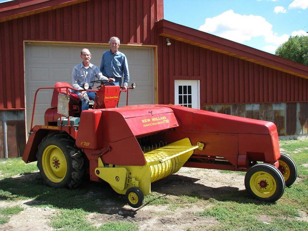 The Fetcher brothers — Bill, left, and Jay — pose on the 1959 Hay Cruiser baler restored by Bill and put back into light use this summer on the Fetcher Ranch near Clark. The photo re-creates a nearly identical image taken 54 years ago when the self-propelled baler first arrived at the ranch.