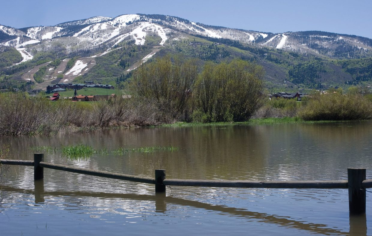 The bottom rails of a fence near the Yampa River are submerged by rising water in Steamboat Springs in June, creating spring's version of a three-wire winter.