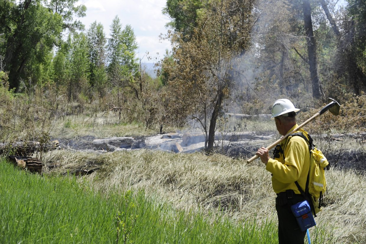 West Routt Fire Protection District Chief Bryan Rickman looks over the fire Tuesday.