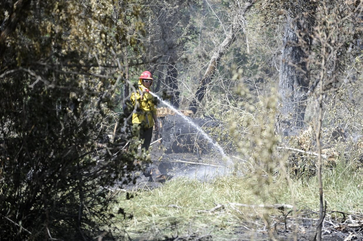 Steamboat Springs Fire Rescue firefighter Devin Borvansky works at the fire Tuesday.