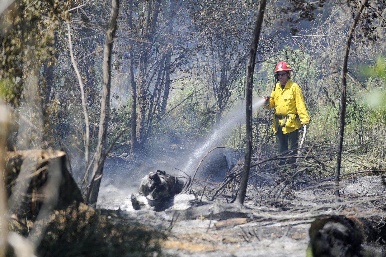 Steamboat Springs Fire Rescue firefighter Brian Shively works at the fire Tuesday.
