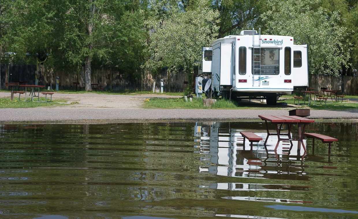 A picnic table in one of several campsites that are flooded at Steamboat Campground in west Steamboat Springs sits in several inches of water Monday morning. The campground is still open.