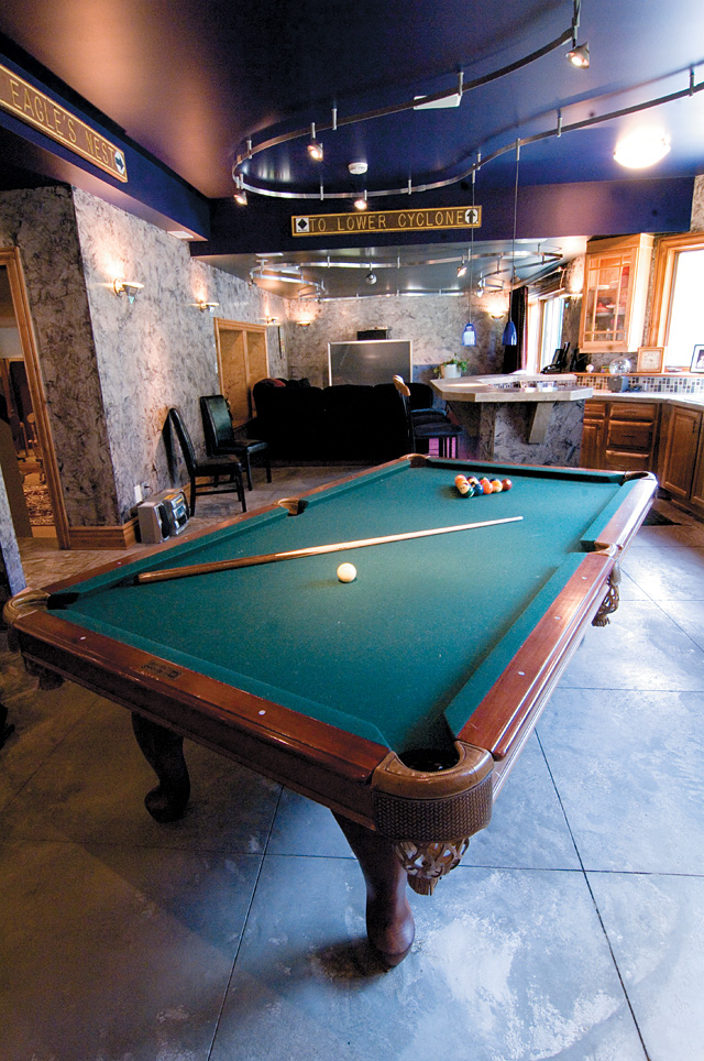 """Built on """"green"""" practices doesn't mean that Mike Roberts' home is short on the extras. The bottom floor is open, allowing for a pool table, bar and television viewing area."""
