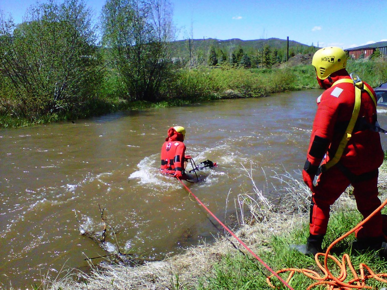 Oak Creek Fire Protection District Capt. Jeff Buffetti heads toward a car that crashed into the Yampa River on Wednesday south of Phippsburg. Yampa Fire Protection District Capt. Ralph Bracegirdle assisted in the rescue.