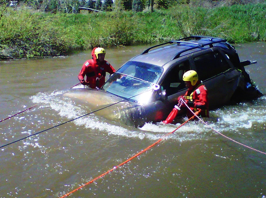 Yampa Fire Protection District Capt. Ralph Bracegirdle and Oak Creek Fire Protection District Capt. Jeff Buffetti work to remove a car that crashed into the Yampa River south of Phippsburg on Wednesday.