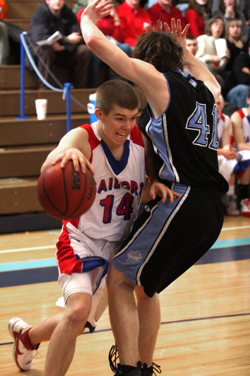 Connor Moore of the Steamboat Sailors drives past Ryan Larson, No. 41, of Pueblo West, during playoff action, the Sailors came up short, falling to the Cyclones, 67-61