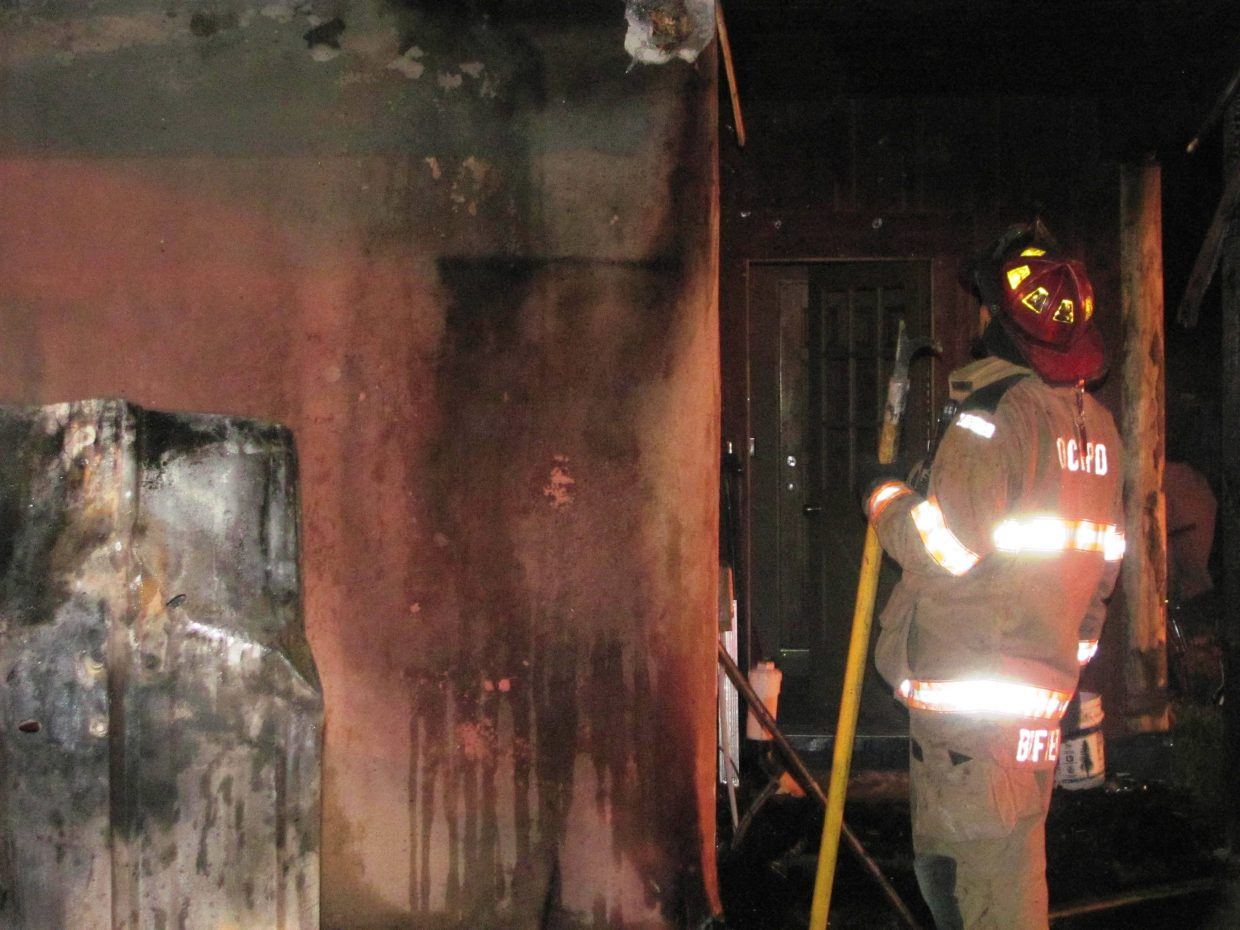 Oak Creek Fire Protection District firefighters work to put out a fire at 134 W. Williams St. on Tuesday. The cause of the fire is still unknown.