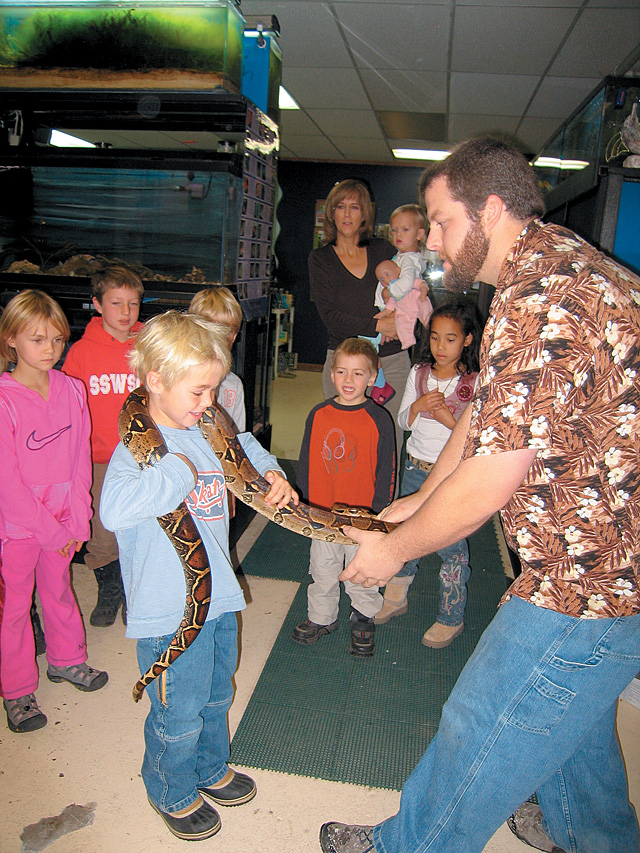 Gavin Graham, right, shows Max, a first-grader from Lowell Whiteman Primary School, a snake during an educational field trip put on by Tropical Rockies. The students were learning about live coral reefs, snakes, lizards and starfish during the hands-on experience.