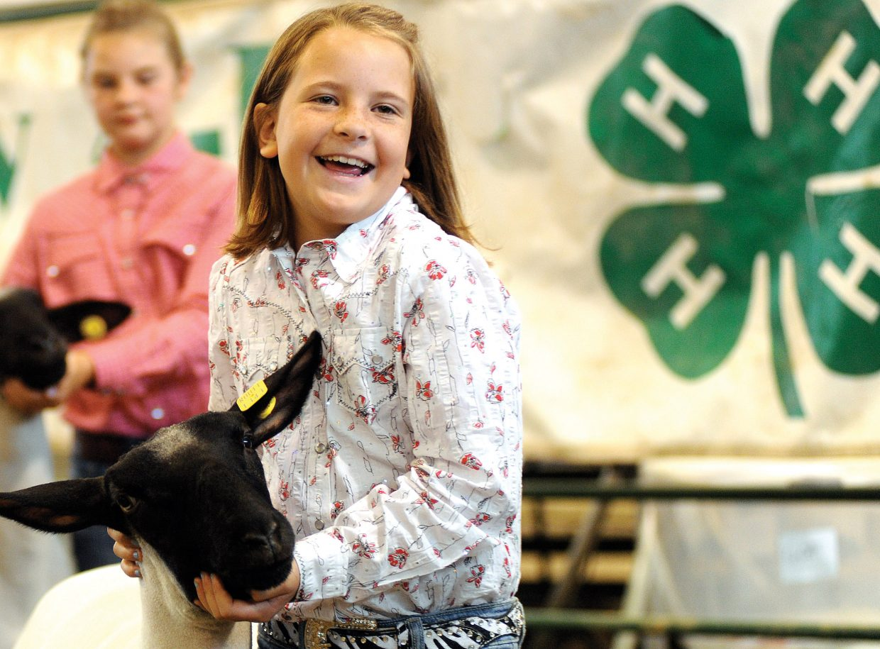 Kayla Wille, 8, laughs while leading her lamb around the arena Thursday during the lamb showmanship competition at the Routt County Fair in Hayden.