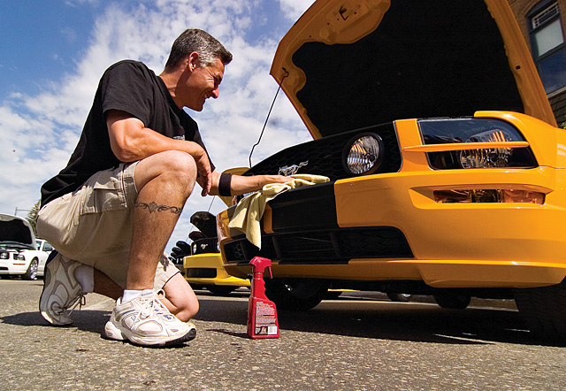Ford Mustang owner David Butler, from the Loveland area, finishes polishing the front grill and bumper of his car before the beginning of judging during the annual Rocky Mountain Mustang Roundup's Show n' Shine car show Saturday morning on Lincoln Avenue.