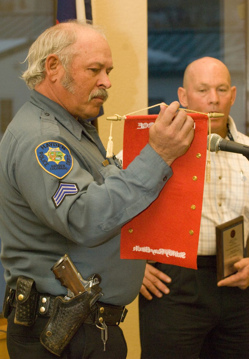 Hayden police Sgt. Gordon Booco hands police chief Ray Birch a cloth scroll with a collection of pins that the Hayden police officers worn while Birch was serving in Iraq during a reception Monday evening in Hayden.