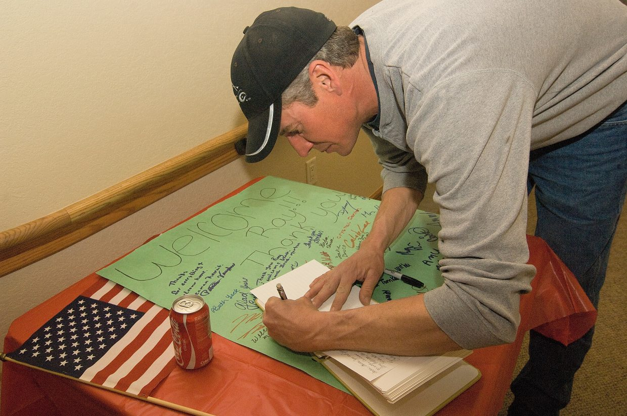 Dave Bantam signs a guest book outside a reception for Police Chief Ray Birch, who returned after spending 191 days in Iraq.