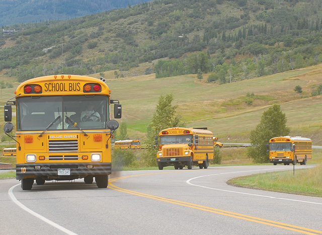 """Steamboat Springs School District buses drive up Amethyst Drive on Monday afternoon, the first day of a new school year in Steamboat Springs. This year brings a new principal to Strawberry Park Elementary School and temporary classrooms to """"Camp Soda Creek"""" downtown, where Soda Creek Elementary School students will attend classes while a new school is built."""