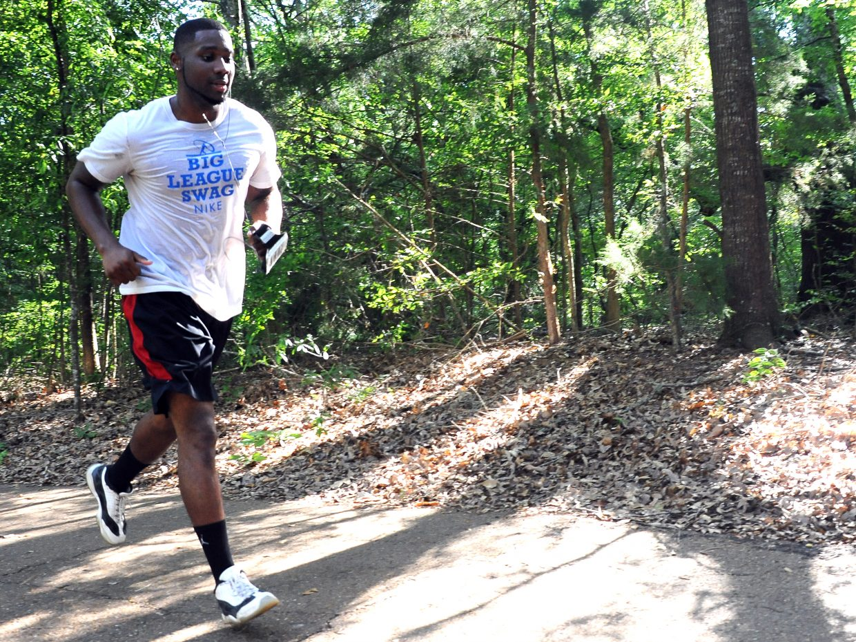 Anthony Fisher runs on a shaded walking and jogging trail in Lexington, Miss. Fisher, 22, began gaining weight after he finished playing basketball in high school. He dedicated himself to losing weight and now works out regularly, in part to help inspire his younger brother, who plays basketball for a local small college. Losing the weight meant cutting local favorites like fried chicken out of his diet.