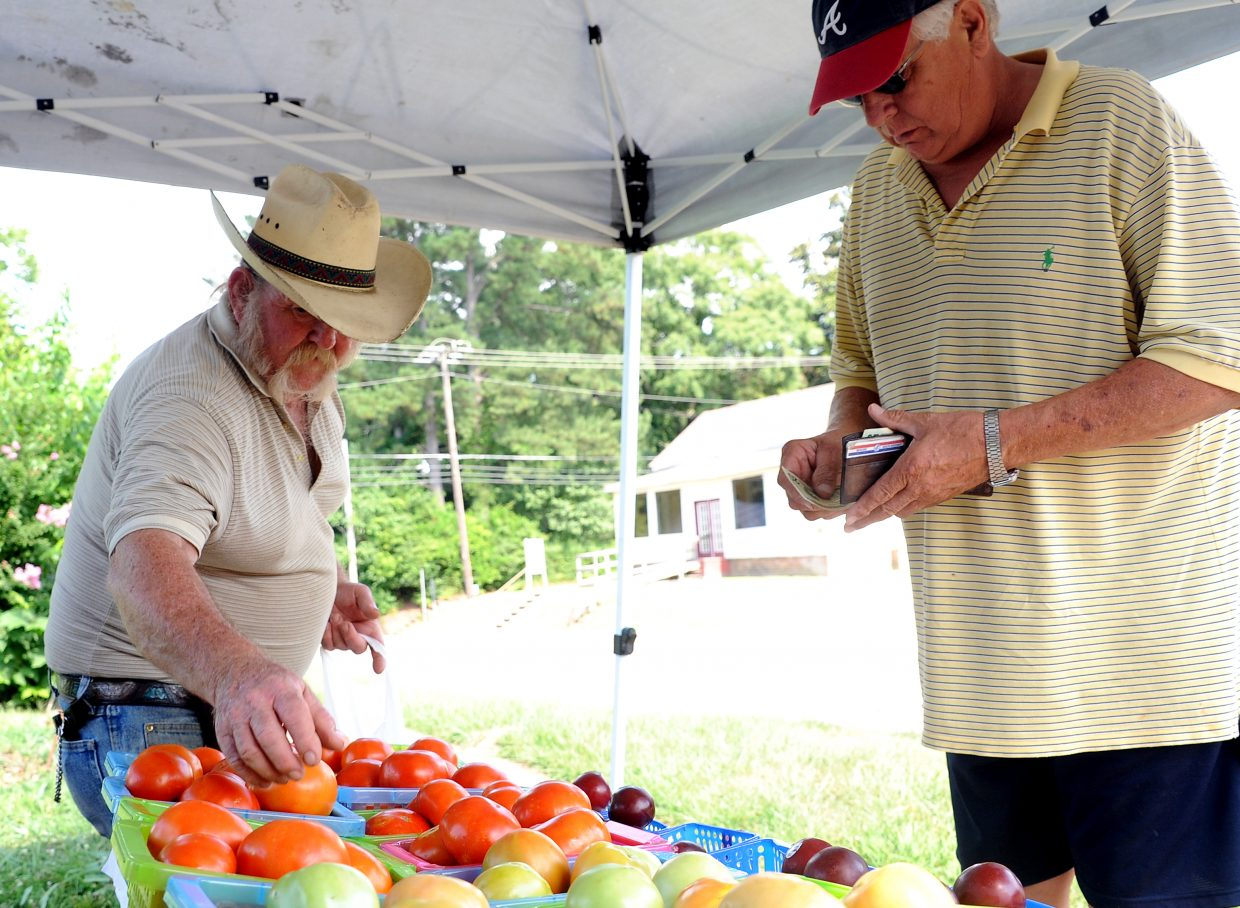 Elvis Jennings, left, sells a basket of tomatoes in Lexington, Miss., on a hot July afternoon. Jennings also runs a leather shop in town but sells tomatoes, watermelons and other fruits and vegetables next to his building. He makes several trips each summer to Arkansas to stock up. Despite his endeavors to cater to Lexington's healthy eaters, he doesn't always partake in healthy meals himself, admittedly opting too often for gas station fried chicken two blocks away.