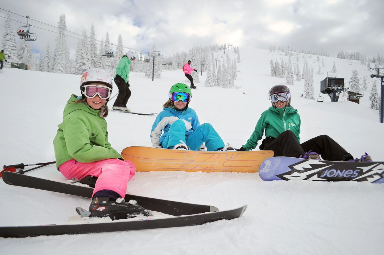 From left, Kaela Pedersen, Gwyneth Moore and Tiffany Moore strap on their snowboards before heading down the slopes near Four Points Lodge on Steamboat Ski Area's Opening Day in 2014.