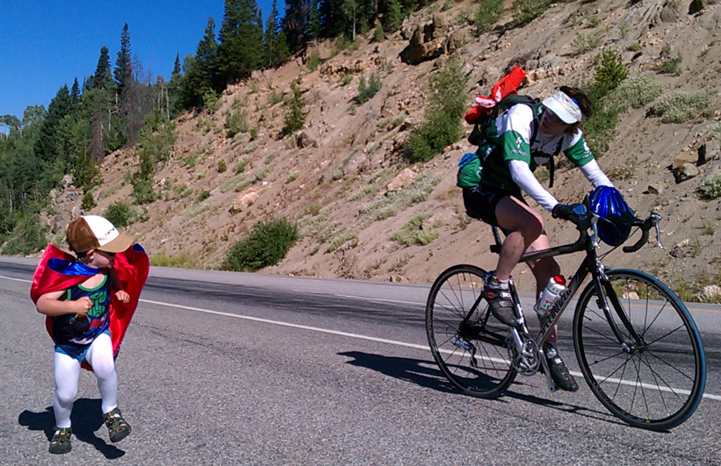 Owen Wither, 6, runs next to a biker on Rabbit Ears Pass while waiting for the USA Pro Challenge riders to arrive from Breckenridge. Submitted by Scott Wither.