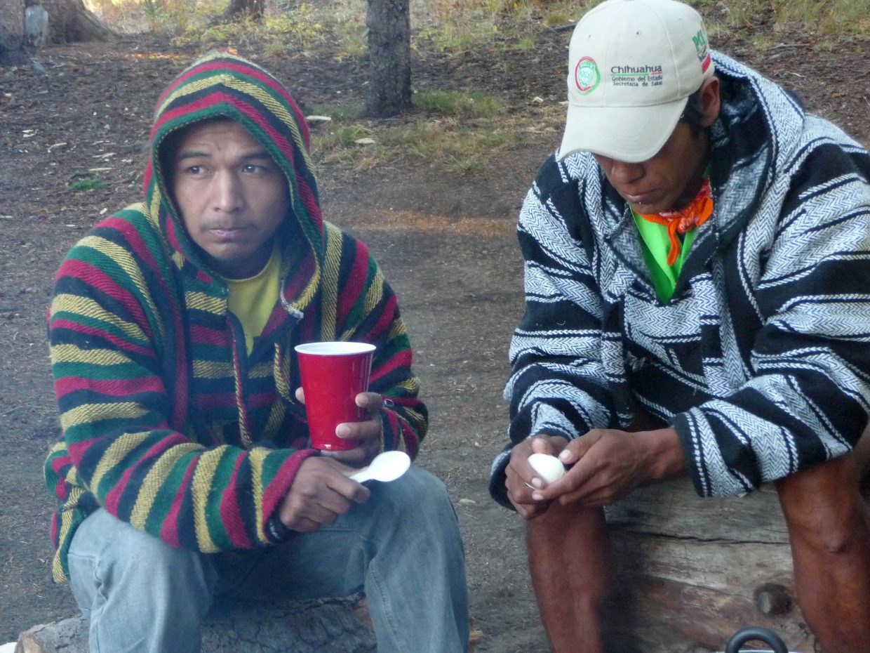 Miguel Lara, left, and Arnulfo Quimare sit around a camp fire Thursday. The two decorated Tarahumara runners will compete in Friday's 100-mile Run Rabbit Run race.