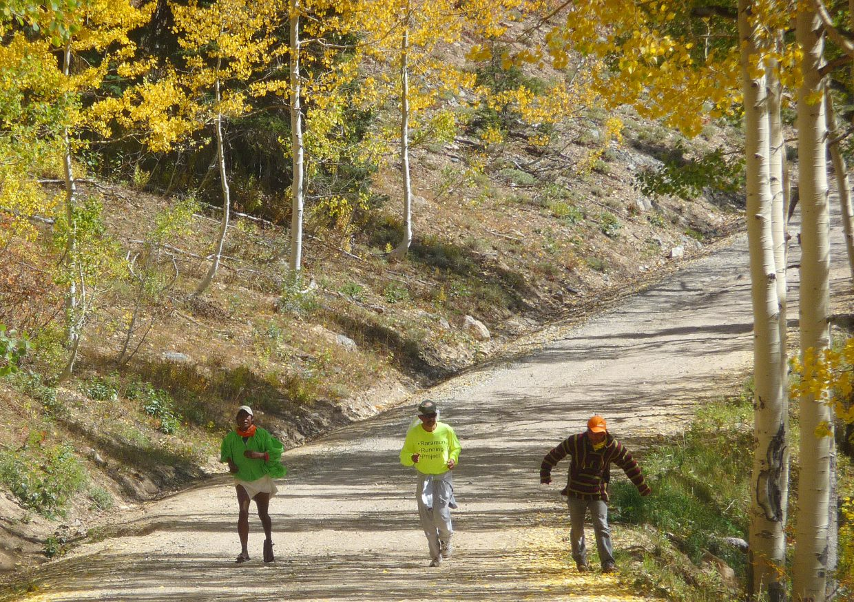 Arnulfo Quimare, left, Gustavo Lozano and Miguel Lara play rarajipari on Thursday on their way down from Buffalo Pass. The game involves kicking a wooden ball and running. Quimare and Lara will compete in Friday's 100-mile Run Rabbit Run.