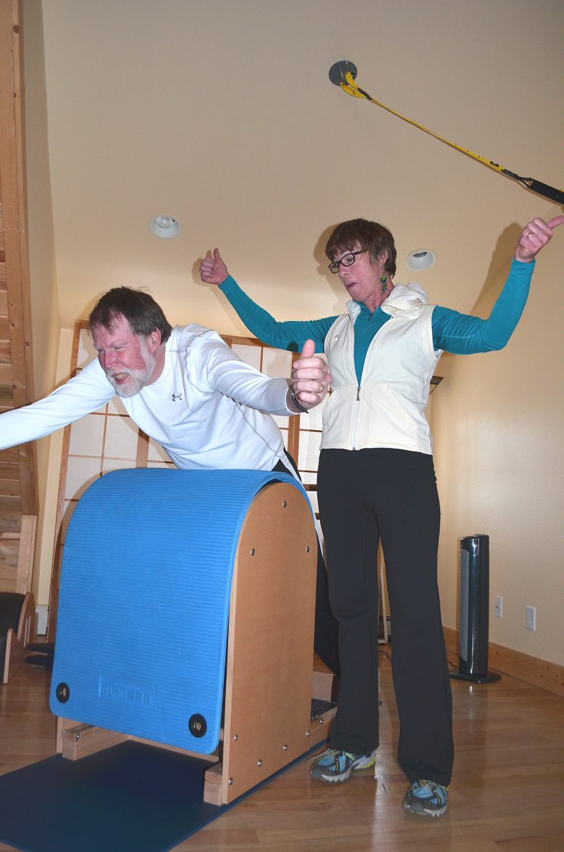Parkinson's patient Gardner Bemis, of Steamboat Springs, grits out the last rep in a set of swan lifts with Eva Gibbon, of Hayden Pilates, on Friday. The exercise is intended to help straighten and strengthen his back. Regular exercise forestalls the progressive stiffening of limbs and muscles that can come with Parkinson's.
