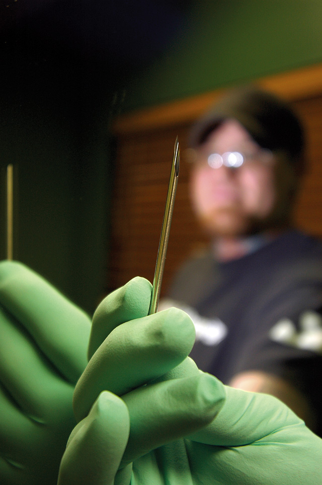 Piercer Jasen Phelps holds a needle used for body piercing.