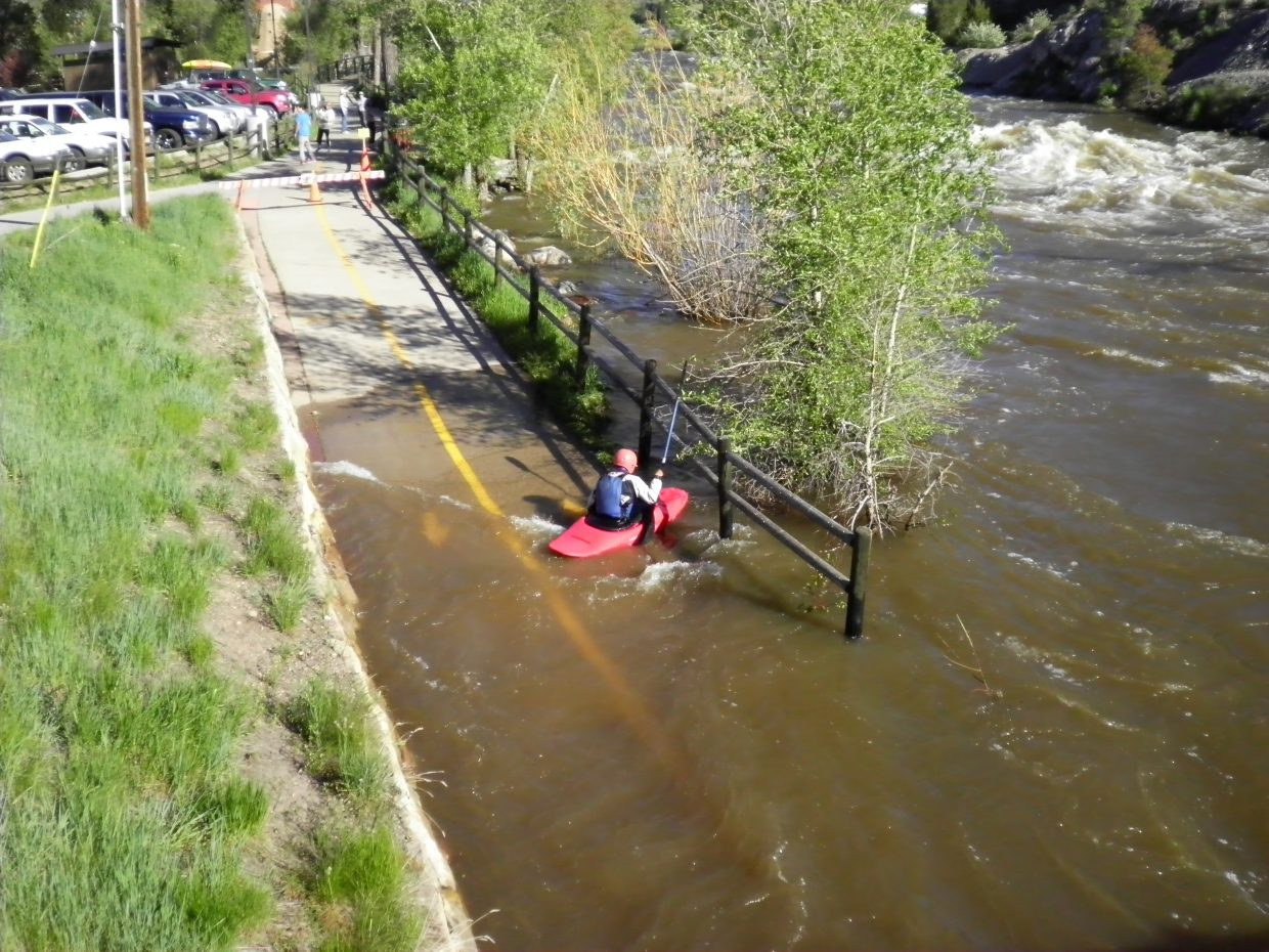 A kayaker uses the bike path as a man-made eddy.