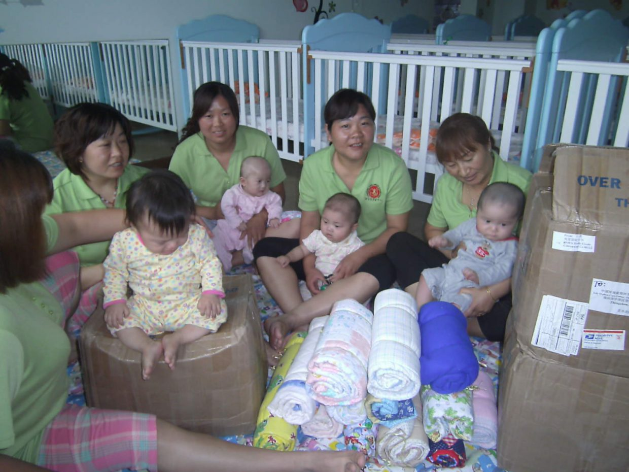 Children at an orphanage in China sit near blankets made and donated by Heritage Christian School students. Read more about the students' efforts and watch a video about the project at www.tinyurl.com/coho78q. Submitted by Tracie Patterson.