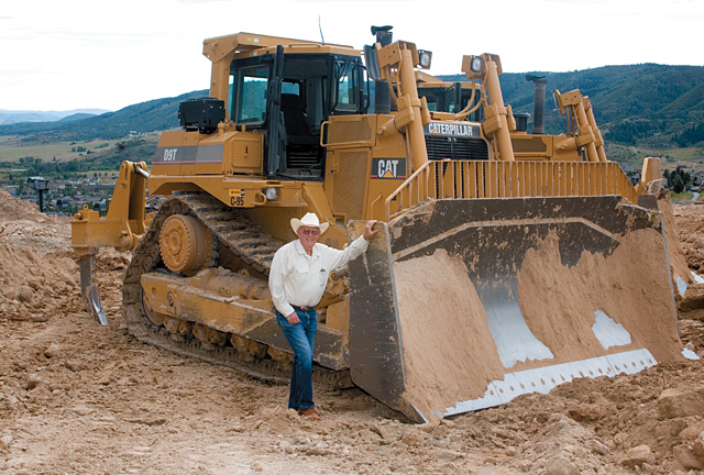 Merle Nash stands beside a modern Caterpillar D-9 bulldozer that is being used to grade the slopes of the Steamboat Ski Area. Nash, and his father Willis's D-7 Caterpillar, played an instrumental role in the formation of many of the ski area's first trails.