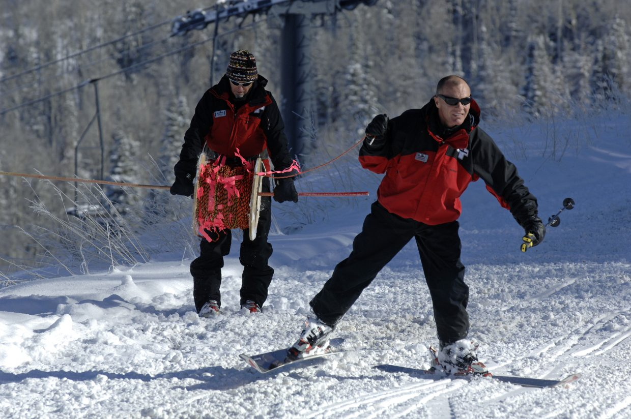 Ski patrollers Johnny Sawyer, left, and John Floyd run rope to set the boundaries for Scholarship Day.