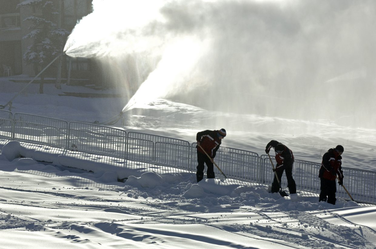 Crews shovels the new snow off of the magic carpet near the base area.