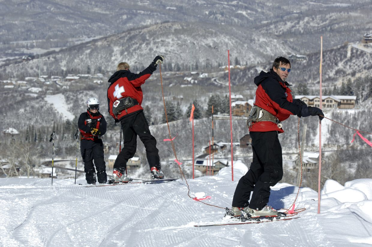 Steamboat ski patrollers, from left, Michele Baxter, Scott Halliday and Johnny Sawyer set up boundaries near the top of Vogue in preparation for Scholarship Day today.