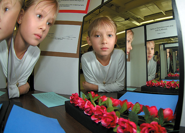 Soda Creek fourth-grader Claire Cohen is reflected in her science fair project while waiting for another group of students to check out her work Thursday. Soda Creek and Strawberry Park elementary schools hosted their fairs Thursday.