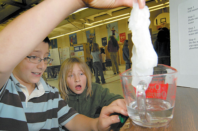 Fifth-grader Cole Sitting demonstrated his science fair project, which tested the absorbency of paper towels, to Kelsey Peters in the gym at Soda Creek Elementary School on Thursday morning. Third-, fourth- and fifth-graders completed projects and displayed them as part of the fair.
