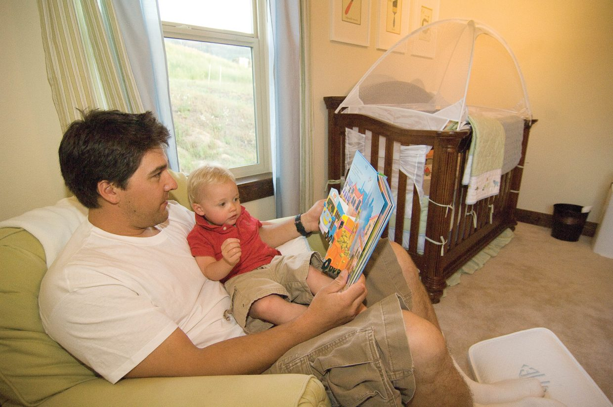 Matt Murphy reads to his son, Cole, inside the family's Red Hawk Village home in Stagecoach. The Murphys were able to take advantage of a short sale to purchase the home.