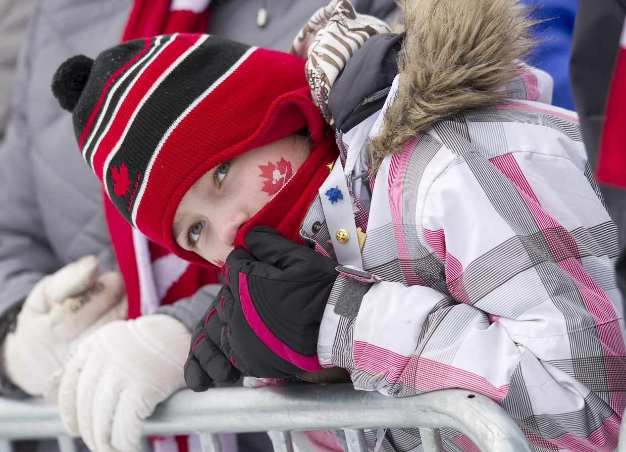 Hayley Frandsen came dressed to support the Canadians in Thursday's Nordic combined event. She looks uphill for a ski jumper during one of the many delays in Thursday's event at Whistler Olympic Park.